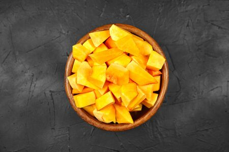 Pumpkin pieces in a round wooden bowl on black table, top view. Chopped pumpkin (butternut squash) in salad dish. Cooking vegetable food Banque d'images