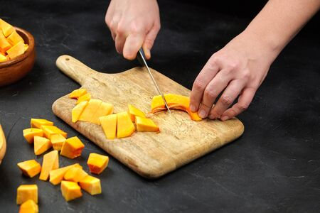 Person cutting a pumpkin on wooden chopping board on stone table. Female hands with steel knife, butternut squash pieces