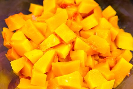 Pumpkin pieces in a deep transparent glass bowl on black table. Chopped pumpkin (butternut squash) in salad dish. Cooking vegetable food