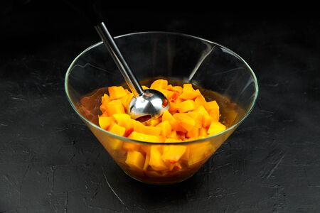 Pumpkin pieces and blender in a glass bowl on black table. Chopped butternut squash in salad dish. Cooking vegetable food, pumpkin puree (mash) recipe Banque d'images