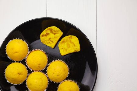 Cupcakes on black plate on wooden table, top view. Halved yellow pumpkin muffin. Homemade bakery, sweet dessert on white background, flat lay. Plant-based food