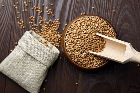 Buckwheat groats (hulled seeds) in bowl, wooden scoop, burlap bag on wooden bacground, top view. Buckwheat whole grains on brown table, flat lay. Superfood, healthy gluten-free food Stok Fotoğraf