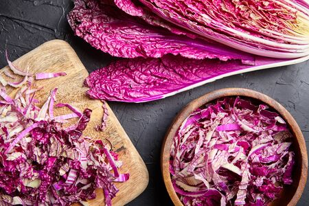 Chopped Red Chinese cabbage (Purple wombok) on wooden cutting board and bowl on stone table. Red Napa cabbage with vibrant colored leaves on black background. Cooking vegetable salad, healthy food