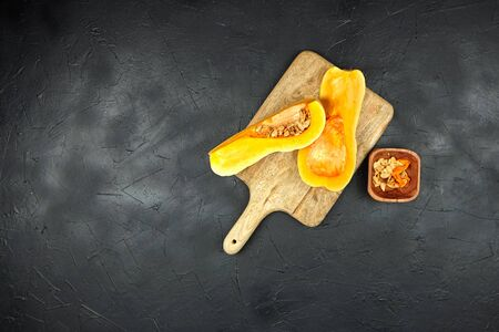 Butternut squash pieces, wooden bowl with pumpkin seeds, cutting board on black background with copy space, top view. Cooking winter squash