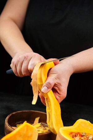 Butternut squash, woman cuts pumpkin peel. Female hands with steel knife, wooden bowl on black background. Cooking sweet winter squash