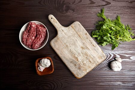 Cooking minced meat. Cutting board with fresh seasonings on a wooden table, flat lay. White garlic heads and cloves, green dill and parsley leaves. Bowl with raw ground beef and condiments, top view Standard-Bild