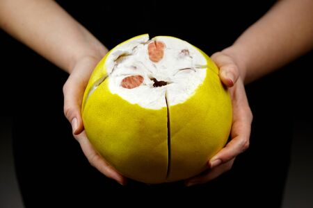 Pomelo citrus fruit with sweet red flesh and yellow thick rind on black background. Fresh juicy shaddock (Citrus maxima). Woman peels pomelo