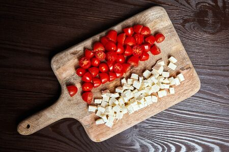 Fresh red cherry tomatoes with salad cheese on cutting board on brown wooden table, top view 免版税图像