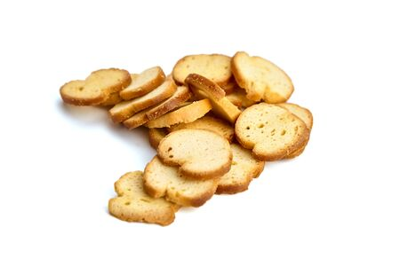Bruschette chips, heap of dry slices of baked bread, scattered beer snack, isolated on white background, selective focus