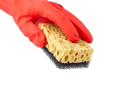 Household sponge from reticulated foam isolated on white background. Hand in red rubber glove holding a yellow black sponge for washing dishes Standard-Bild