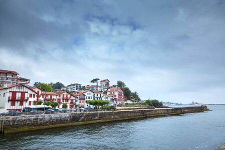 Embankment in Cibour, Basque Country, France. European town with traditional red and white half-timbered basque houses, typical architecture. Coastal town on the shore of the Bay of Biscay Standard-Bild