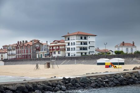 Sandy beach, traditional houses and stone embankment of Saint-Jean-de-Luz, Basque Country, Atlantic coast, France. Coastal french town at cloudy sky summer day. Sea shore