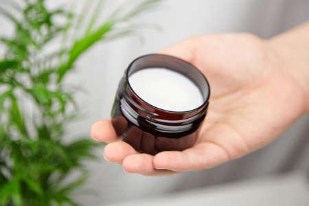 Dark jar with organic pure shea butter base oil in female hand. Natural moisturizing cosmetics.