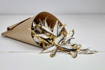 Dried small salted sprat or kilka fish in paper bag on white wooden table background. Standard-Bild
