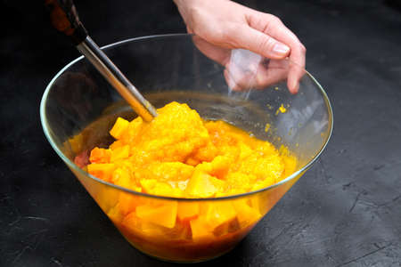 Pumpkin pieces and blender in a glass bowl on black table. Chopped butternut squash in salad dish. Cooking vegetable food, pumpkin puree (mash) recipe Standard-Bild