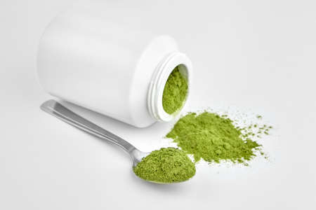 Freeze dried young organic wheatgrass powder in teaspoon and jar on white background. Vegan food supplement.