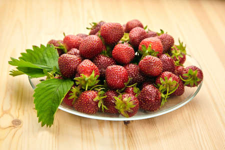 Heap of strawberries with green leaves on a plate on wooden table. Red ripe berries, fresh juicy strawberries
