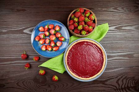 Homemade strawberry tart on green linen napkin with fresh berries on wooden table background, top view