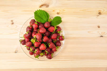 Strawberries on a transparent glass plate on wooden background with copy space. Red ripe berries, fresh juicy strawberries, top view