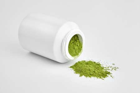 Organic wheatgrass powder in plastic jar. Detox superfood. Green food supplements. Standard-Bild