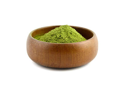 Wheatgrass powder in wooden bowl isolated on white background. Alternative medicine, herbal nutritional supplement.