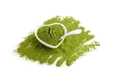 Wheatgrass or barley grass powder in ceramic bowl and spoon isolated on white. Detox superfood. Vegan-friendly supplement. Standard-Bild
