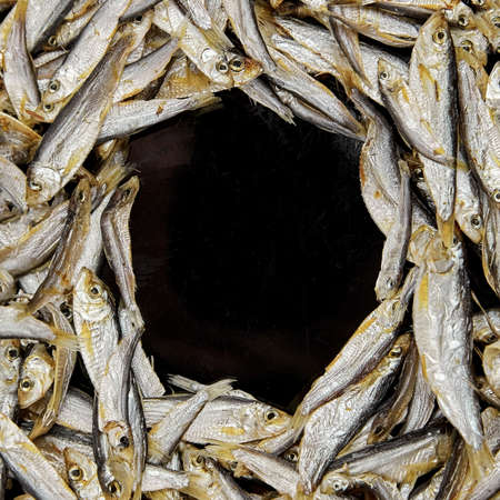Dried small salted sardelle or tulka fish border texture. Food background, top view, copy space.