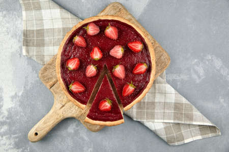 Strawberry pie with fresh berries halves on gray stone background. Sweet summer desser on wooden cutting board, top view. Piece of pie, napkin. flat lay