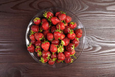 Strawberries on a transparent glass plate on wooden background, top view. Red ripe berries, fresh juicy strawberries on brown table
