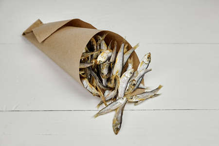 Small salted dried fish in paper bag on white wooden table background. Beer appetizer. Standard-Bild
