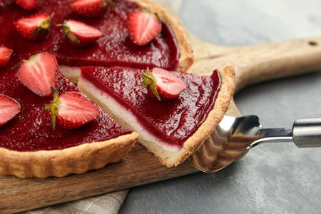 Strawberry pie with fresh berries. Cake shovel with piece of pie on blurred background. Sweet summer dessert, halves of ripe strawberry, fruit topping Standard-Bild