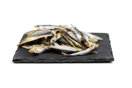Small dried fish on black slate board isolated on white background