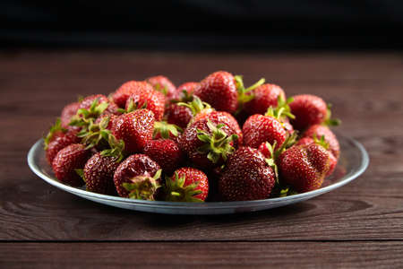 Strawberries on a transparent glass plate on wooden background. Red ripe berries, fresh juicy strawberries