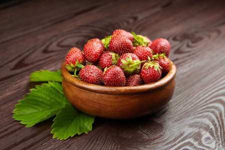 Strawberries with green leaves in wooden bowl on brown table. Red ripe berries, fresh juicy strawberries on wooden background, selective focus Standard-Bild