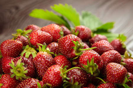 Fresh ripe strawberries with green leaves on blurred wooden background, closeup. Red summer berries Standard-Bild