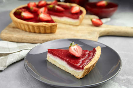 Piece of strawberry pie with fresh berries topping on gray plate on gray stone background. Sweet dessert Standard-Bild