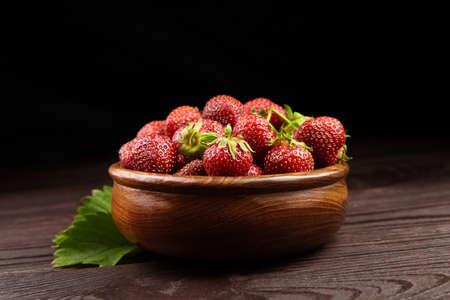 Strawberries with green leaves in wooden bowl on brown wooden table. Red ripe berries, fresh juicy strawberries on dark background Standard-Bild