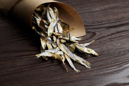 Sun-dried salty small fish. Stockfish in paper bag on dark wooden background.