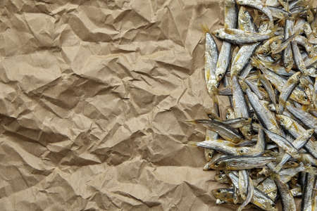 Dried small salted sardelle fish stack on crumpled parchment paper background. Top view, copy space.