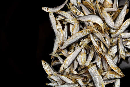 Dried salted small fish on black background, top view, copy space. Standard-Bild