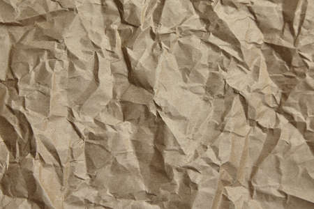 Crumpled paper, texture, background. Brown craft paper with wrinkled pattern, top view