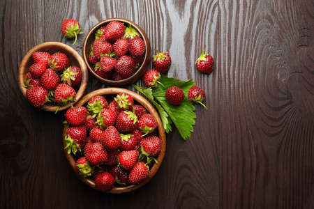 Strawberries with green leaves in wooden bowls on brown table, top view. Red ripe berries, summer food, fresh juicy strawberries on wooden background with copy space