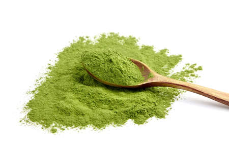 Freeze dried young wheatgrass powder in wooden spoon isolated on white background. Vegan food supplement.