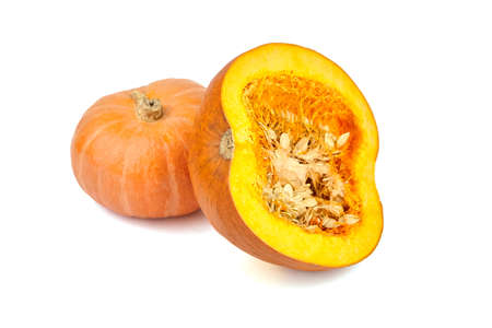 Pumpkin half with seeds, whole orange squash isolated on white background.