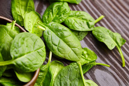 Spinach fresh green leaves in a wooden background. Healthy food, herbal ingredient. Heap of spinach on a brown table
