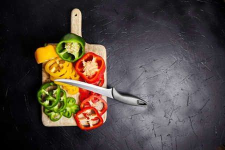 Cutting board with slices of red, green, and yellow bell peppers on black background. Knife and sliced sweet peppers on stone table. Vegetable salad ingredient, cooking healthy food, top view