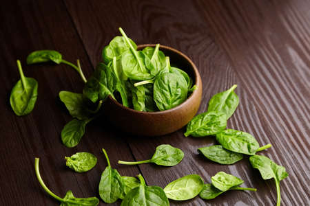 Spinach fresh green leaves in a bowl on wooden background. Healthy food, salad dish, herbal ingredient on a brown table