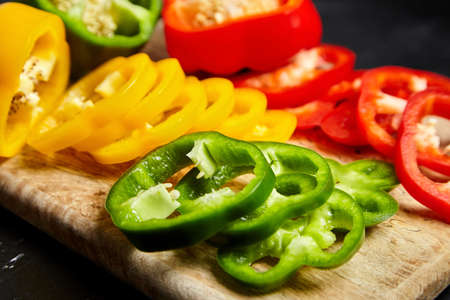 Slices of red, green, and yellow bell peppers on a wooden cutting board, closeup. Sliced sweet peppers in different colors, vegetable salad ingredient, cooking healthy food Banque d'images