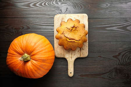 Homemade autumn pumpkin cake with fresh pumpkin on wooden cutting board on dark background, top view Reklamní fotografie