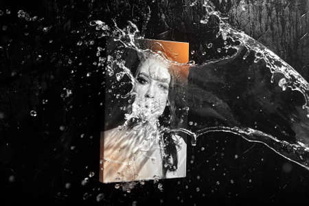 Photo printed on canvas with gallery wrap technique, splashing water drops on black background. Woman portrait, wall decor. Photography with protective coating, waterproof ink, selective focus